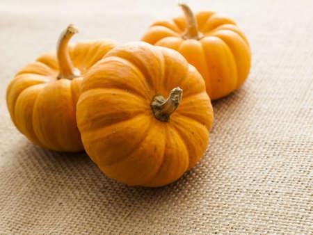 Small orange pumpkins on burlap fabric.