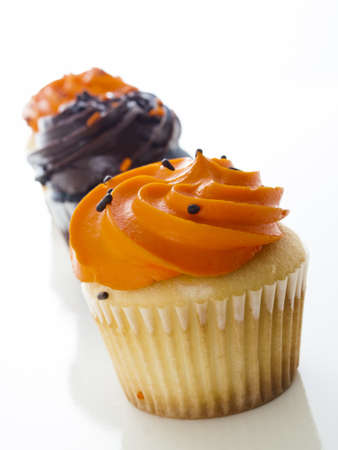 Halloween orange and black cupcakes on white background.