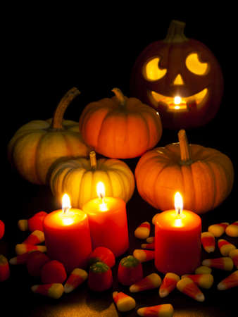 vegetabilis: Lit orange candles with small pumpkins and jack-o-lantern on black background.
