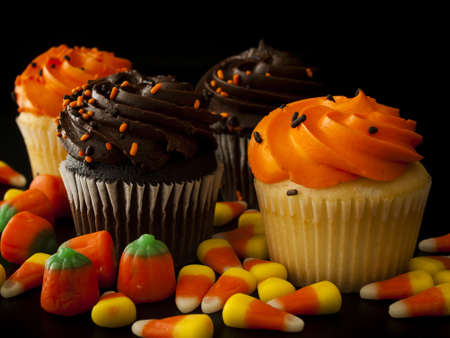 candy corn: Halloween orange and black cupcakes with candy corn candies on black background.