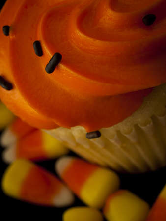 patty cake: Halloween orange and black cupcakes with candy corn candies on black background.