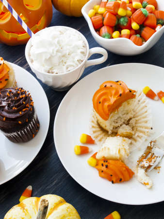 Eating Halloween cupcakes with orange and black icing.