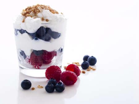yogur: Fruto delicioso, yogur griego y parfaits de granola en el fondo blanco