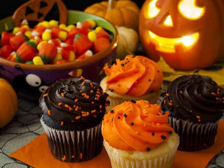 Halloween cupcakes with orange and black icing on orange napkin.