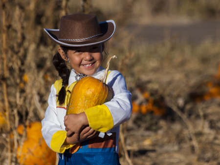 vegetare: Little girl in Halloween costume looking for big pumpkin on pumpkin patch.