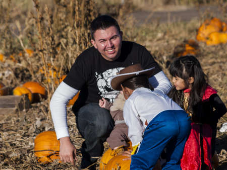 Young family with kids in costumes looking for big pumpkin on pumpkin patch. photo