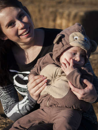 Young mother with her toddler in Halloween costume in corn maze. photo