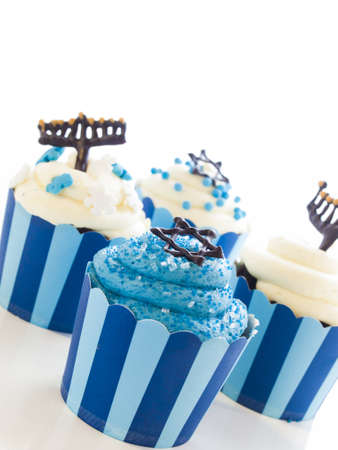 Gourmet cupcakes decorated with white and blue icing for Hanukkah.