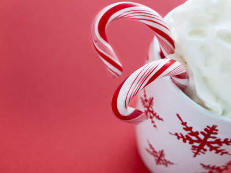 hot cocoa: Hot chocolate with whip cream and peppermint canes on red background. Stock Photo