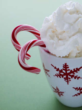 Hot chocolate with whip cream and peppermint canes on green background. photo