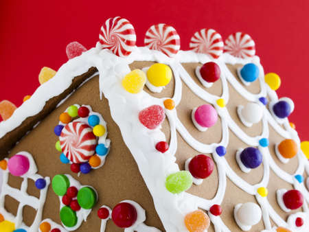 Decorated gingerbread house on red background.