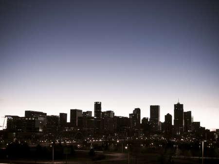 denver skyline with mountains: Skyline of downtown Denver at sunrise.