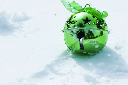 Green christmas bell in virgin snow. photo