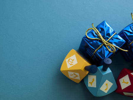 Colorful dreidels with presents on blue background. photo