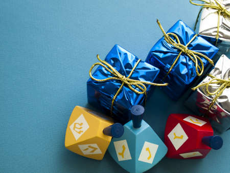 chanukkah: Colorful dreidels with presents on blue background. Stock Photo