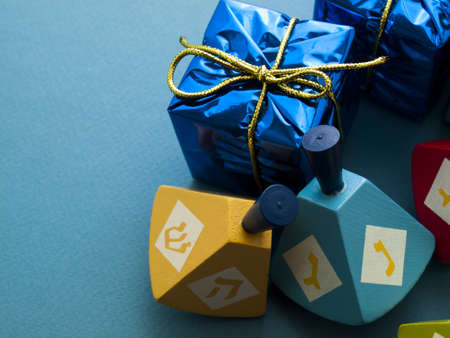 khanukah: Colorful dreidels with presents on blue background. Stock Photo