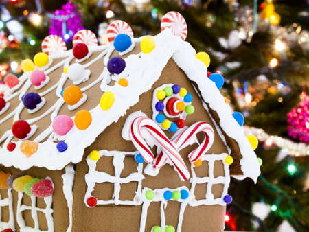 Gingerbread house decorated with candies with Christmas tree in the backgound. photo