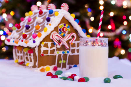 a house with a straw: Gingerbread house with glass of milk and red straw.