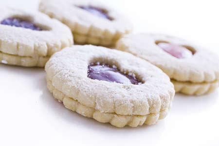 Linzer Torte biscotti su sfondo bianco con lo zucchero a velo spruzzato sulla parte superiore.