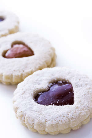 Linzer Torte cookies on white background with powdered sugar sprinkled on top. photo