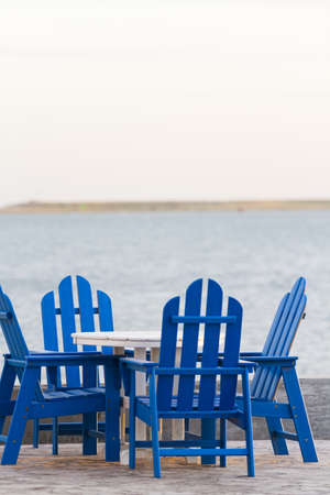 distanation: Pation with blue furniture on the beach.