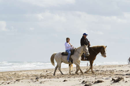 Horeseback riding on the beach of South Padre Island, TX. Stock Photo - 17175266
