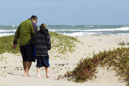 Father and son walking on the beach of South Padre Island, TX. photo