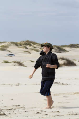 fine particles: Teenage boy walking on the beach of South Padre Island, TX.
