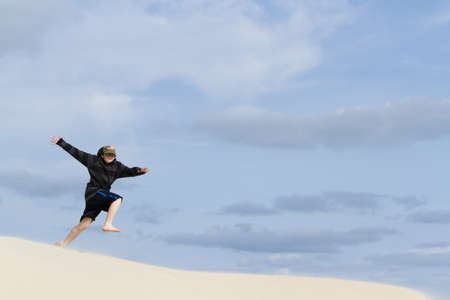 fine particles: Teenage boy jumping on the coastal dunes of South Padre Island, TX.
