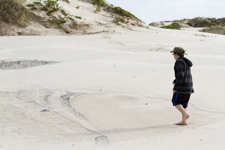 Teenage boy walking on the beach of South Padre Island, TX. photo