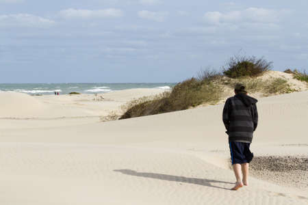 cameron county: Teenage boy walking on the beach of South Padre Island, TX.