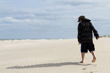 cameron county: Teenage boy walking on the beach of South Padre Island, TX.
