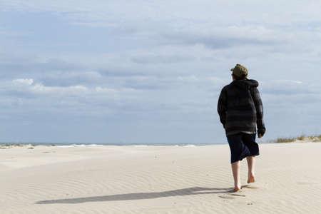 distanation: Teenage boy walking on the beach of South Padre Island, TX.