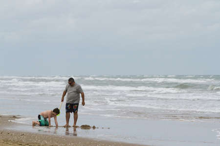 cameron county: Father and son playing on the beack of South Padre Island, TX.