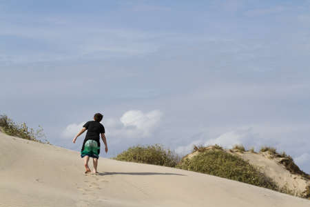 Teenager walking on coastal dunes of South Padre Island, TX. Stock Photo - 17198590