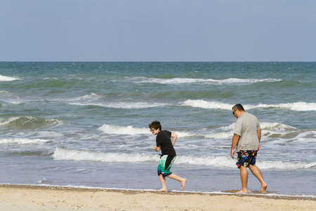 beack: Father and son playing on the beack of South Padre Island, TX.