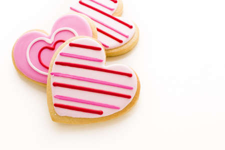 baked treat: Heart shaped cookies decorated fancy icing patterns.