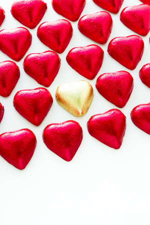 foil: Heart shape chocolate candies wrapped in red foil for Valentines Day.
