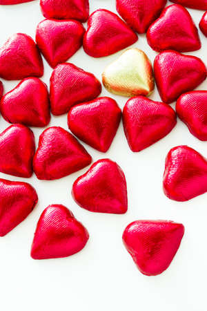 Heart shape chocolate candies wrapped in red foil for Valentines Day.