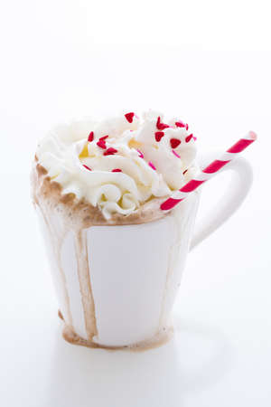 Messy hot chocolate with white and red straw. photo