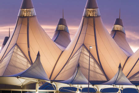 Glowing tents of DIA at sunrise. Denver International Airport well known for peaked roof. Design of roof is reflecting snow-capped mountains.