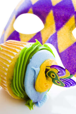 Fancy cupcakes decorated with leaf and mask for Mardi Gras party. Stock Photo - 17489875
