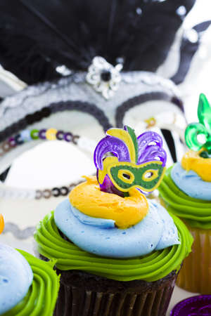 Fancy cupcakes decorated with leaf and mask for Mardi Gras party. Stock Photo - 17489924