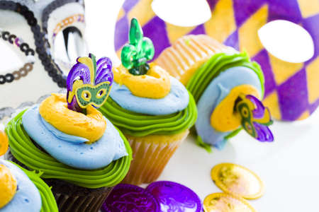 Fancy cupcakes decorated with leaf and mask for Mardi Gras party. Stock Photo - 17489934