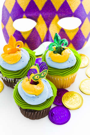 Fancy cupcakes decorated with leaf and mask for Mardi Gras party. Stock Photo - 17489869