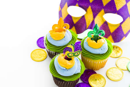 Fancy cupcakes decorated with leaf and mask for Mardi Gras party. photo