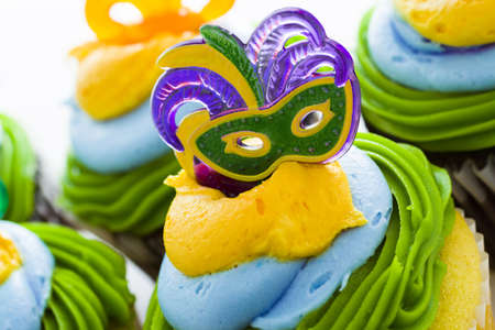 Fancy cupcakes decorated with leaf and mask for Mardi Gras party. Stock Photo - 17489799