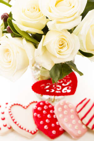 Gourmet cookies with bouquet of white roses. photo