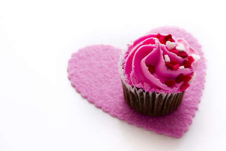 Chocolate cupcake with pink icing decorated for Valentines Day. photo
