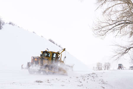heavy industry: Yellow snowplow clearing rural road from snow.